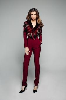 Modèle à la mode avec des cheveux bruns en salopette bordeaux