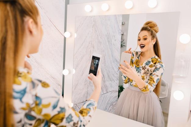 Modèle à la mode avec coiffure élégante, maquillage professionnel faisant selfie dans un miroir dans un salon de coiffure