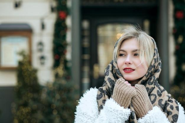 Le modèle à la mode porte un manteau et une écharpe en tricot posant à la ville. espace pour le texte