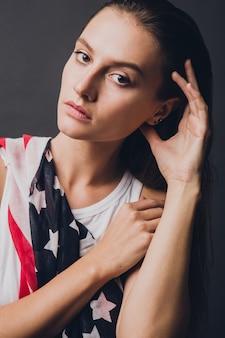 Modèle à la mode qui pose en studio dans une tenue élégante style drapeau américain rock