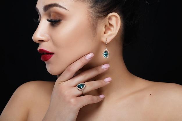Le modèle montre des boucles d'oreilles et une bague avec de belles pierres précieuses bleues
