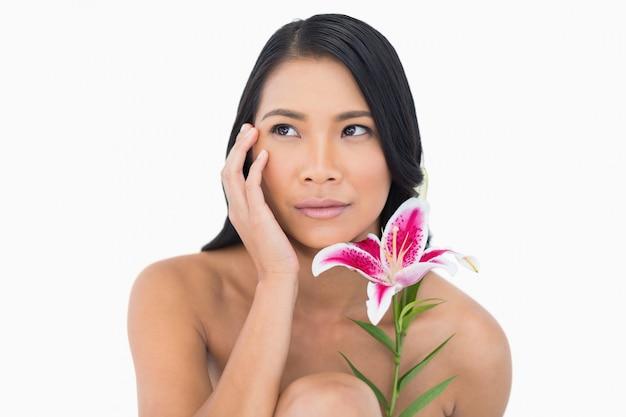Modèle naturel posant avec lis et toucher son visage