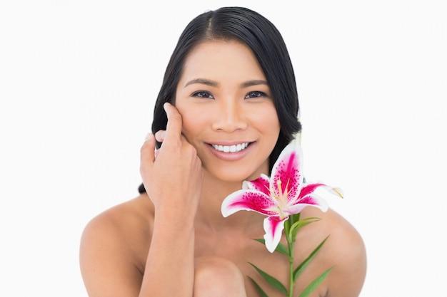 Modèle naturel souriant posant avec lys et caressant son visage