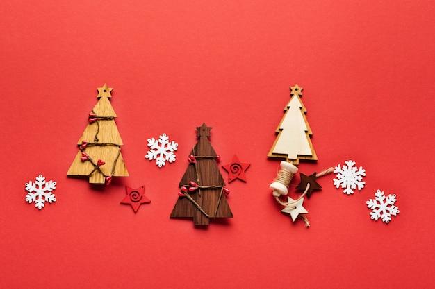 Modèle de noël fait de jouets en bois de sapin de noël, de flocons de neige et d'étoiles sur le rouge.