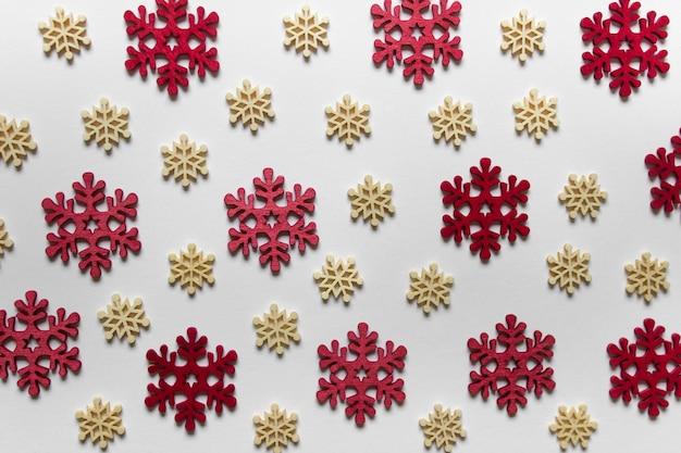 Modèle de noël avec des flocons de neige en bois rouge et jaune sur une surface blanche