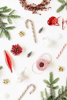 Modèle de noël nouvel an avec des branches de sapin, boules de noël, bonbons, guirlandes, décorations sur blanc