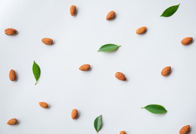 Modèle de noix d'amandes organiser sur blanc avec feuille verte