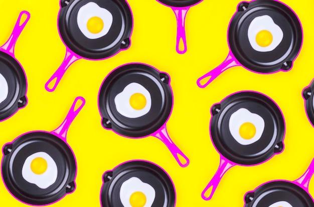 Modèle de nourriture créative avec des œufs au plat sur des casseroles roses sur fond jaune vue de dessus