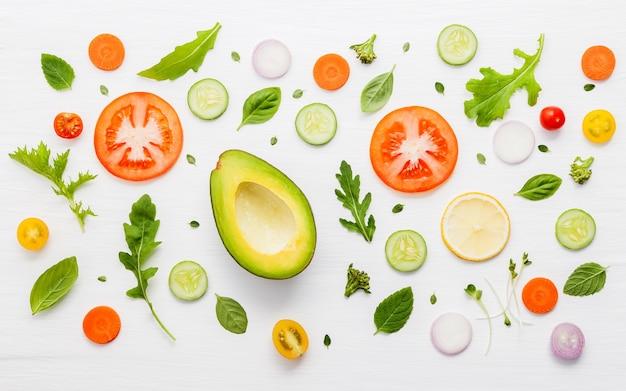 Modèle de nourriture avec des ingrédients bruts de salade sur un fond en bois blanc.