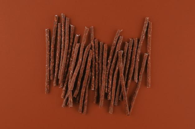 Modèle de nourriture pour chien faite avec des bâtons de collations sèches. texture plate posée dans des tons terreux bruns. animaux domestiques, alimentation des animaux. régime spécial, fournitures de formation.