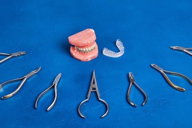 Modèle orthodontique et ensemble d'outils d'orthodontie en métal médical sur bleu