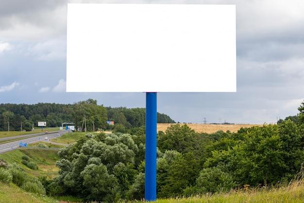 Modèle de panneau d'affichage blanc blanc le long de l'autoroute contre les champs