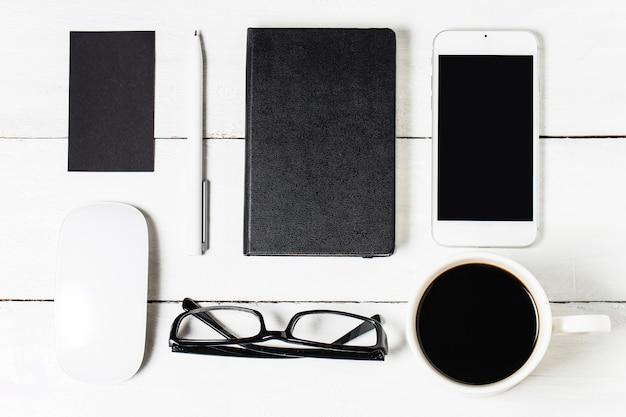 Modèle de paperasserie en blanc pour les concepteurs. maquette de conception réactive sur fond de bois vintage. papier, papier à en-tête, tasse à café, smartphone, crayon et casque sur fond de table en bois. vue de dessus.