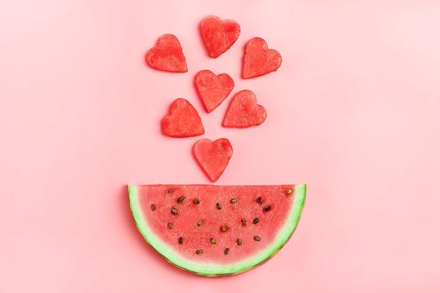 Modèle de pastèque rouge. mise en page créative faite en forme de coeur de melon d'eau sur rose.