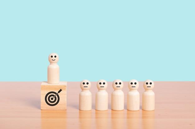 Modèle de personne en bois debout sur le podium parmi les gens sur fond bleu. concept de croissance de la cible commerciale. espace de copie.