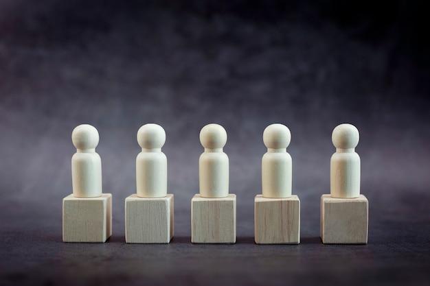 Modèle de personne en bois parmi les gens sur fond noir pastel concept de leadership