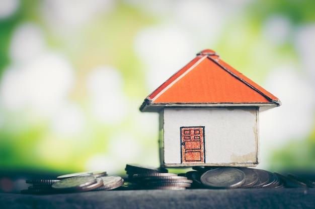 Modèle de petite maison debout sur un tas de pièces de monnaie. le concept d'achat d'habitat.