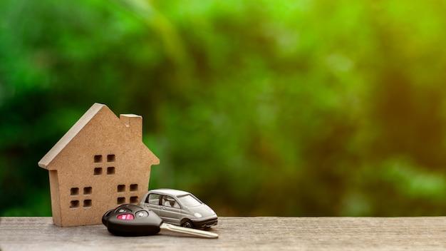 Modèle de petite voiture avec des clés sur un bureau en bois dans la matinée.