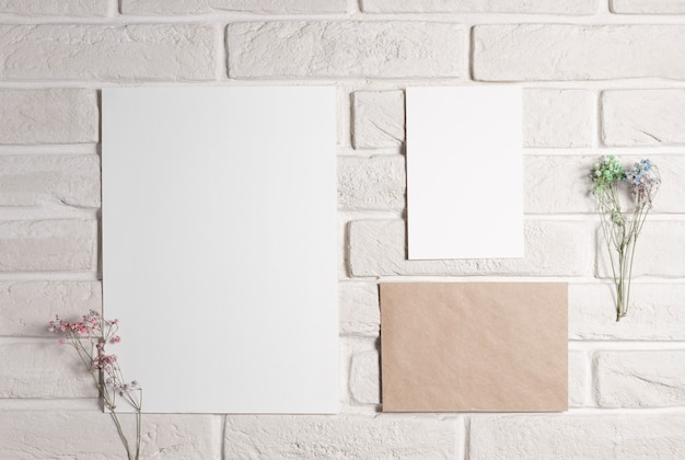 Modèle de planche d'humeur avec des cartes en papier vierge sur un mur de briques blanches avec des fleurs séchées