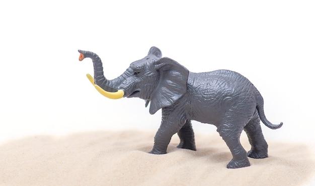 Modèle en plastique d'éléphant avec du sable. jouet éléphant isolé sur blanc.