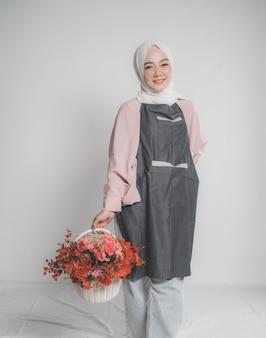 Modèle portant le hijab, tenant une fleur sur fond isolé beige. élégante femme musulmane tenant un seau de fleur