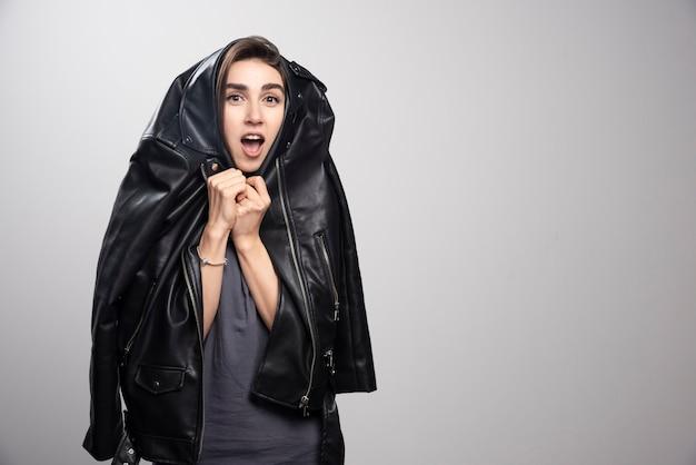 Modèle portant une veste en cuir noir sur fond gris.