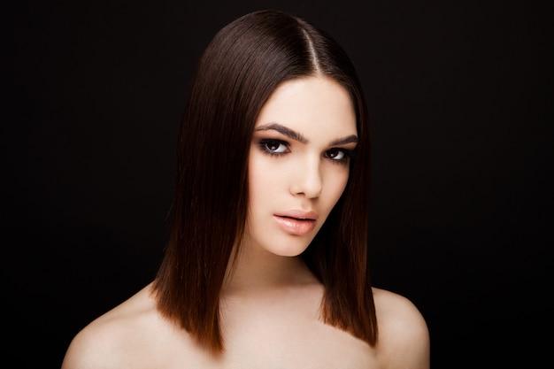 Modèle de portrait de beauté avec une coiffure brune brillante avec des lèvres roses sur fond noir