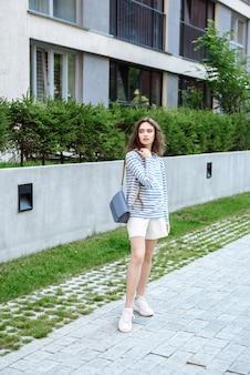 Modèle posant sur fond de rue dans le catalogue de vêtements de la collection été