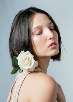 Modèle posant avec rose blanche
