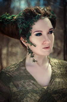 Le modèle pose dans une forêt printanière en tant que faune