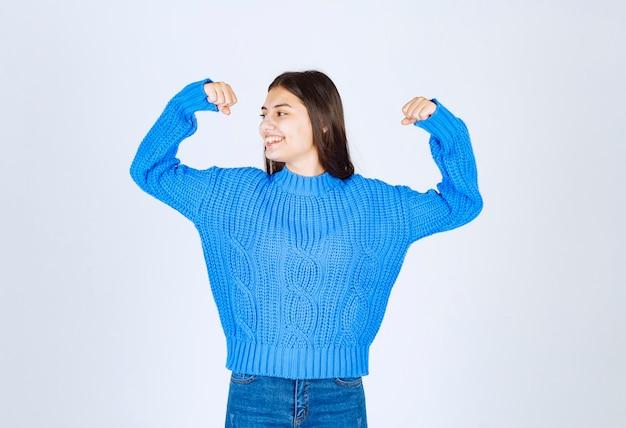 Modèle positif de jeune fille pointant sur ses biceps.