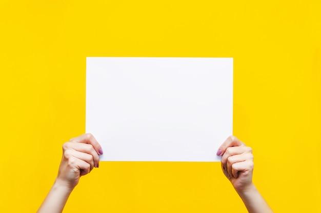 Modèle pour la conception feuille blanche avec un espace de copie vide pour le texte ou la conception dans des mains féminines isolées sur un mur jaune de couleur vive