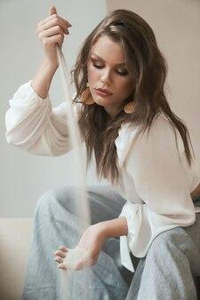 Un modèle professionnel attrayant avec un maquillage et une coiffure à la mode est très élégant en blouse blanche et pantalon gris tout en versant du sable de mer d'une main à l'autre. looks de mode. notion de modélisation