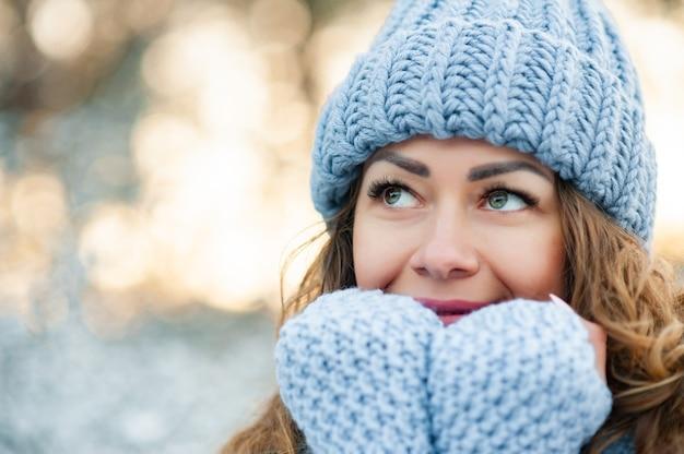 Modèle regardant de côté, portant un pull élégant, un chapeau, des gants.