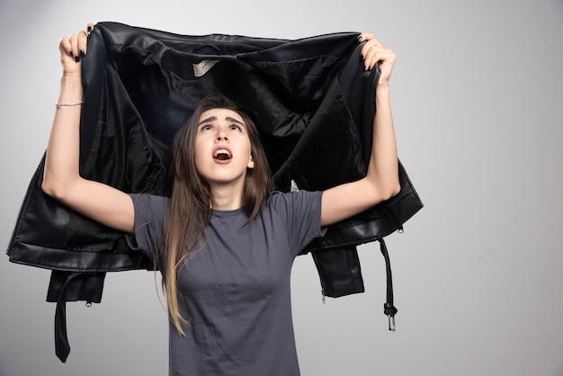 Modèle regardant sa veste en cuir noir sur fond gris.