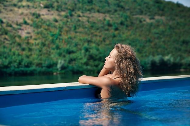 Modèle relaxant dans la piscine sur la nature
