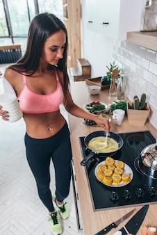 Modèle de remise en forme dans des vêtements de sport préparant un repas faible en glucides dans la cuisine.