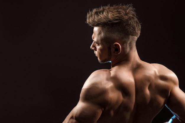 Modèle de remise en forme homme athlétique fort posant les muscles du dos.