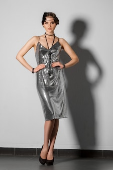 Modèle en robe de guirlandes d'argent de style rétro avec plume dans les cheveux