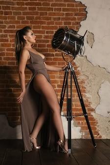 Modèle en robe posant près de la lampe