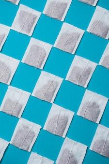 Modèle de sachets de thé blanc fermé diagonal sur fond bleu