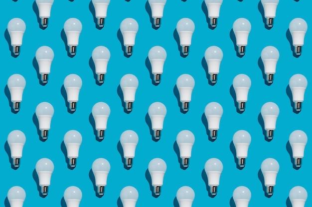 Modèle sans couture d'ampoules à économie d'énergie blanche sur fond bleu.
