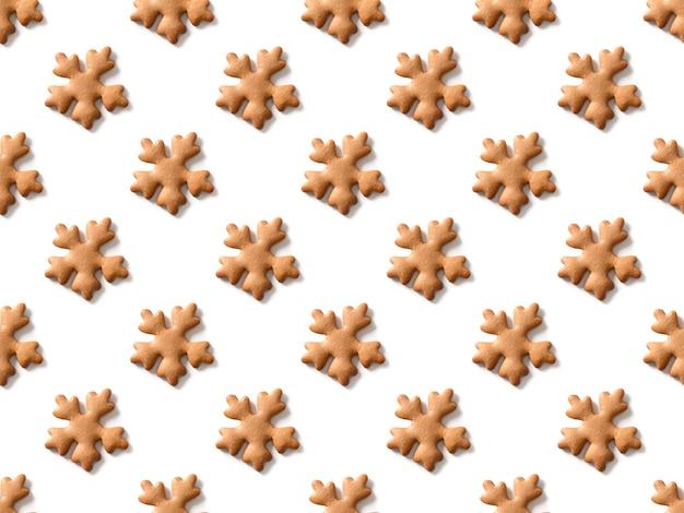 Modèle sans couture de biscuits faits maison de noël comme des flocons de neige sur fond blanc. noël.