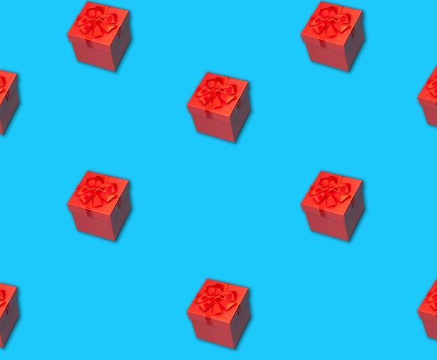 Modèle sans couture de boîte-cadeau rouge avec un ruban sur une surface bleue