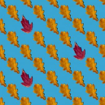 Modèle sans couture de feuilles d'automne sèches jaunes et rouges sur fond bleu. peut être utilisé comme arrière-plan naturel, impression d'automne sur tissu, papier d'emballage