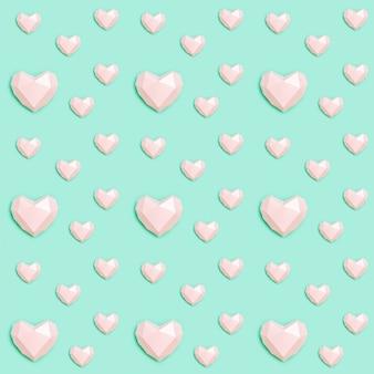 Modèle Sans Couture Avec Forme De Coeur Papier Polygonale Rose Sur Papier De Couleur Menthe. Concept D'amour. Photo Premium