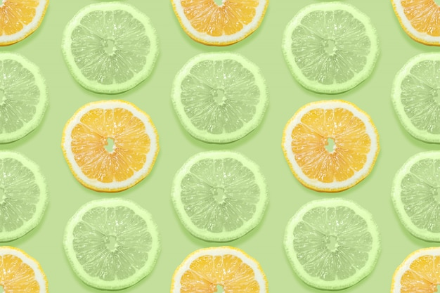 Modèle sans couture de fruits avec des citrons trancher sur fond abstrait vert pastel.