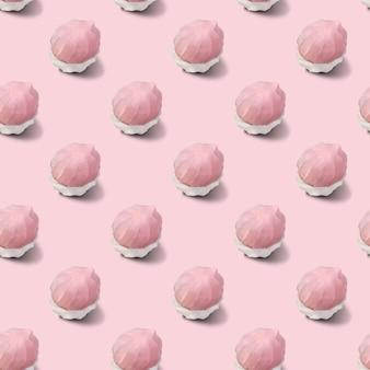 Modèle sans couture de guimauves bicolores blanches et roses sur une surface rose