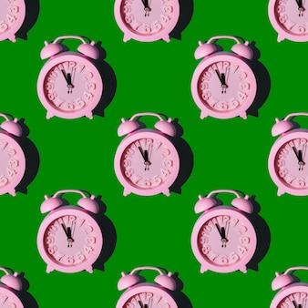 Modèle sans couture avec des horloges roses sur fond vert, répétant le papier peint avec une mise en page transparente minimaliste. concept de nouvel an à minuit. peut être utilisé comme arrière-plan, emballage, élément textile