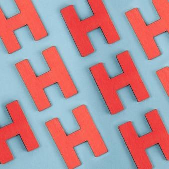 Modèle sans couture de lettres majuscules rouges h sur fond bleu